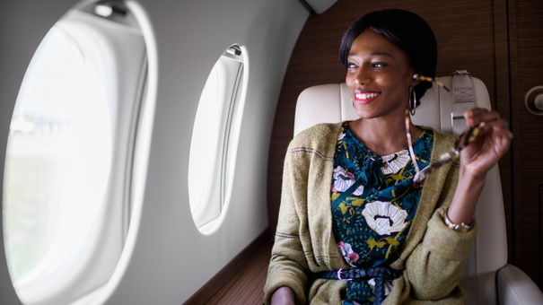 Black woman sitting inside private jet airplane and holding digital tablet